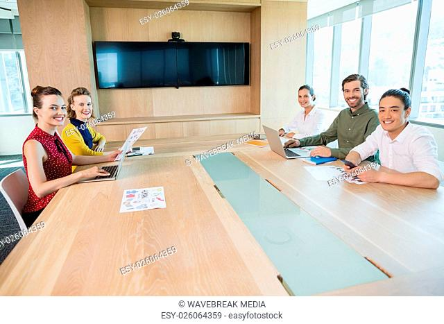 Smiling business team sitting in conference room