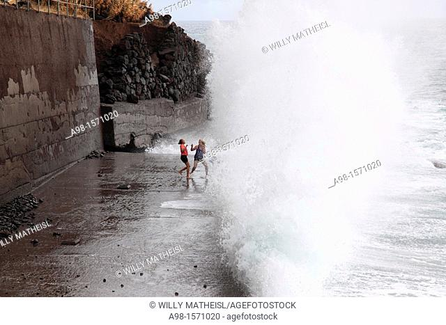 girls playing at the beach and have fun with the spray of waves, Madeira, Portugal, Europe