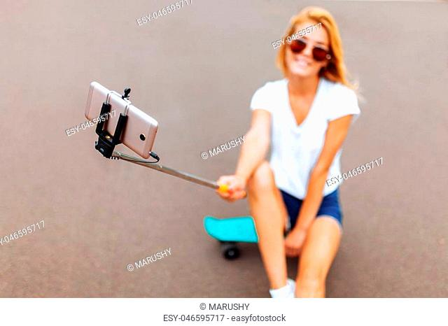 Beautiful girl with a skate, taking a selfie in the Park