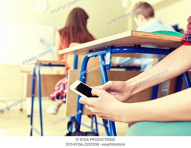 student boy with smartphone texting at school