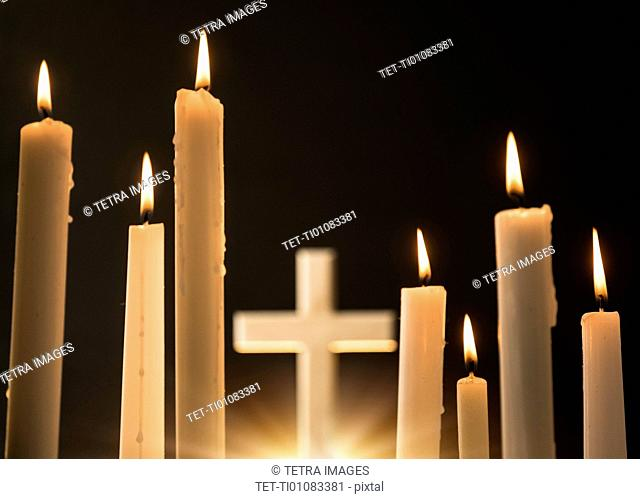 Burning candles with cross in background