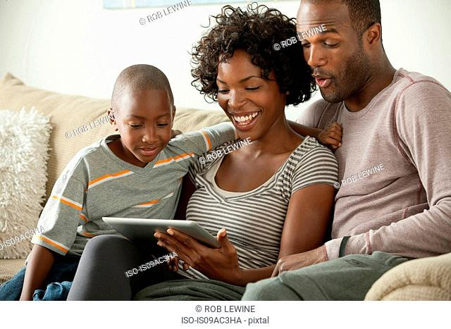 Boy with parents on sofa using digital tablet