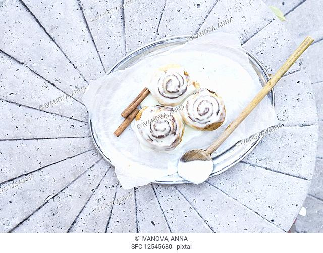 Cinnamon rolls with cream-cheese icing and cinnamon sticks on a silver dish over a light stone background