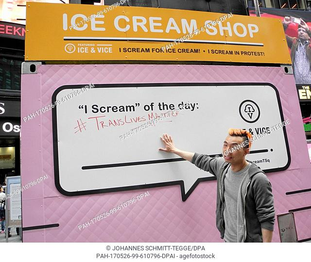 """Ken Lo, employee of the ice cream parlor """"""""I Scream""""""""presents a board on which different sentences are written on a daily basis at the Times Square in New..."""