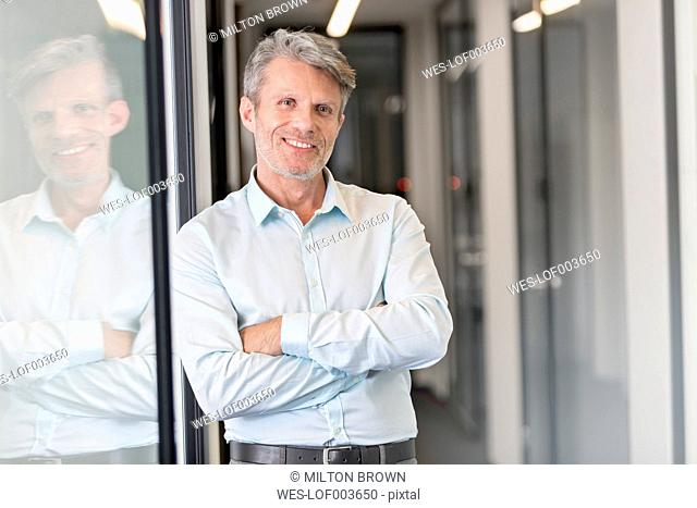 Mature businessman standing in office corridor with arms crossed