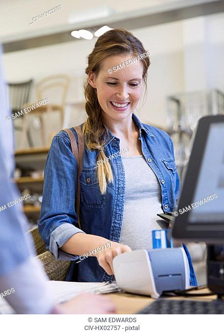 Smiling woman using credit card reader in shop