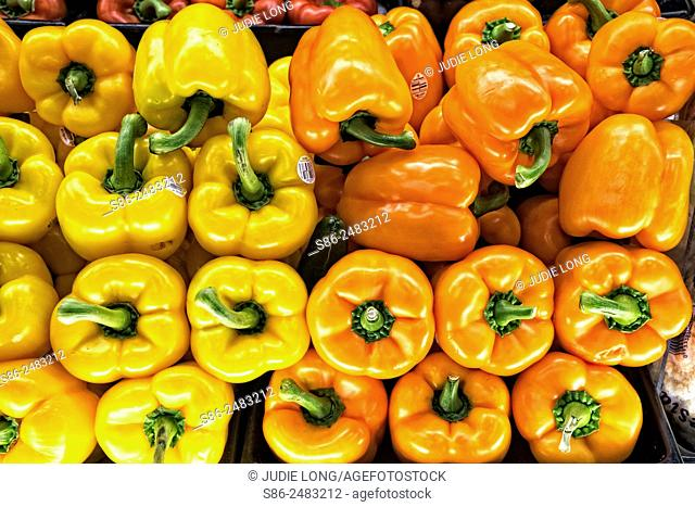 Yellow and Orange Peppers stacked in a supermarket food display. Manhattan, New York City