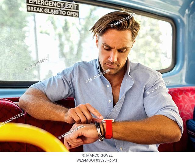 UK, London, man sitting in a double decker bus using smartwatch
