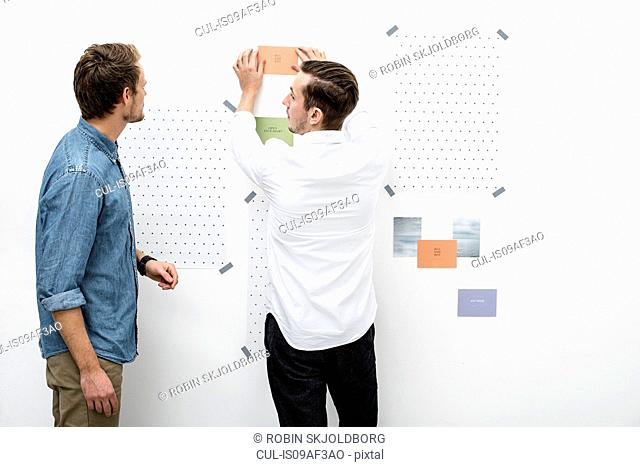 Male colleagues preparing presentation on wall