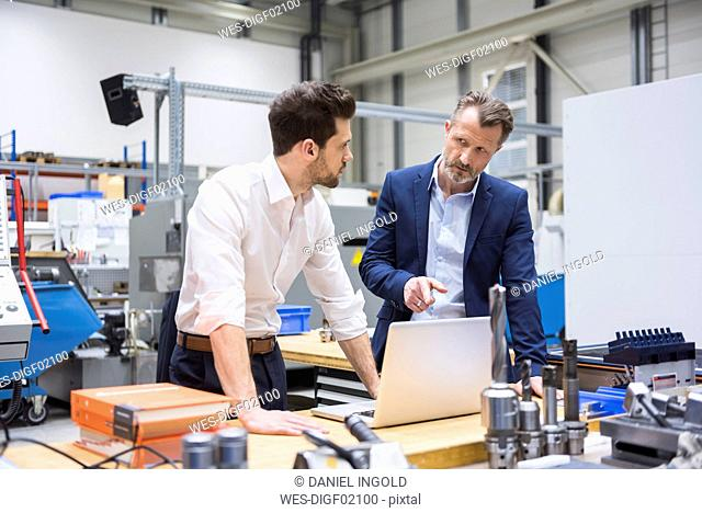 Two men at table in factory shop floor with laptop