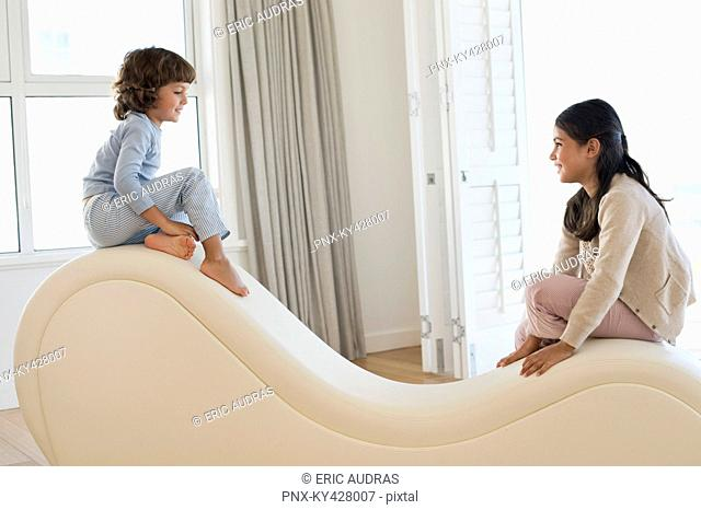 Brother and his sister sitting at the edges of a chaise longue