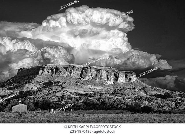 Thunderstorm behind Black Mesa and Adobe church during sunset, Pajartio, New Mexico, USA