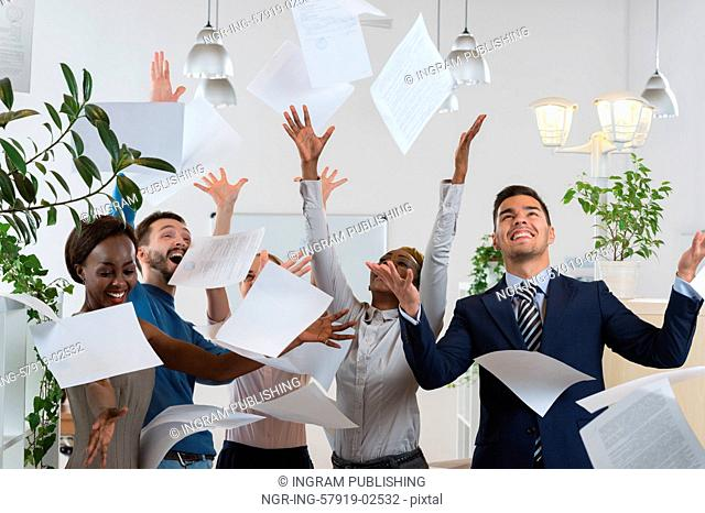 Group of excited multi racial businesspeople throwing papers in office