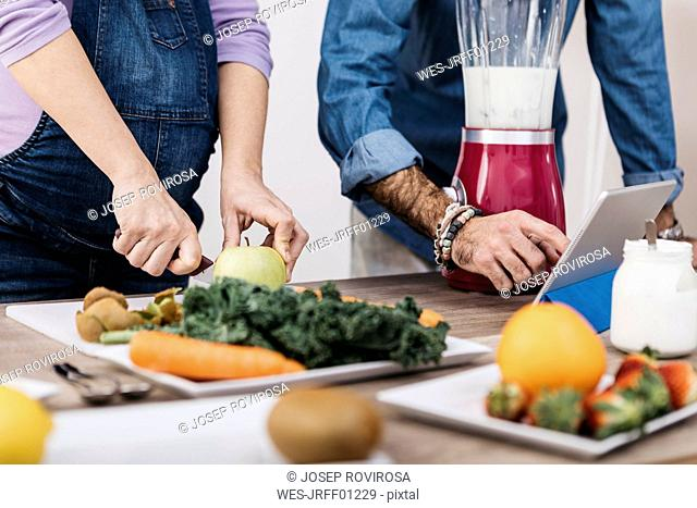 Hands of couple preparing fruits and using tablet for preparing smoothies