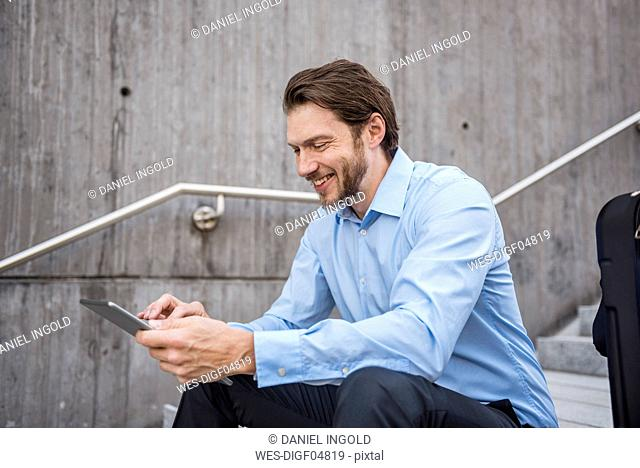 Smiling businessman with suitcase sitting on stairs using tablet