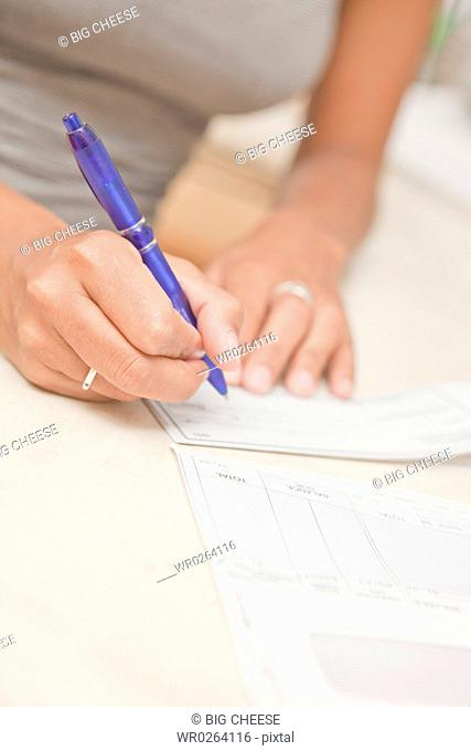womans hand writing checks
