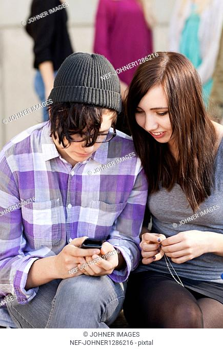 Two teenagers sitting on bench with mobile phone