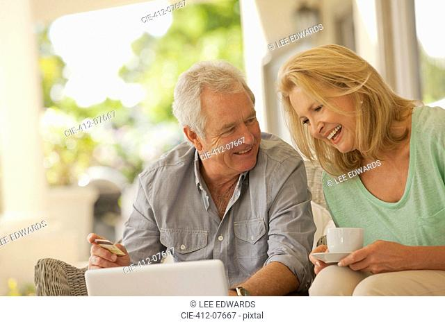 Smiling couple drinking coffee and shopping online on patio