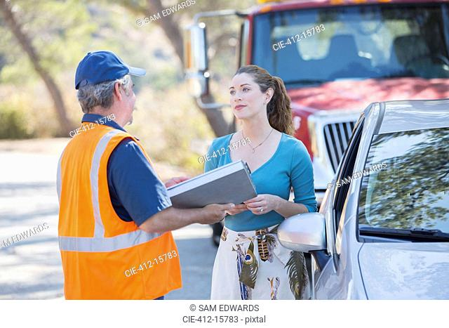 Roadside mechanic talking with woman