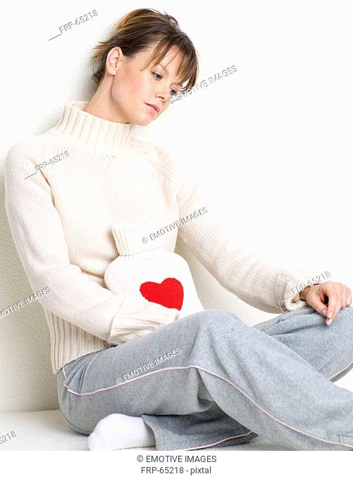 young woman with hot water bottle heart-style