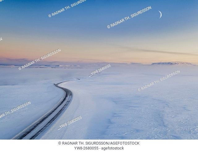 Moon and snowy mountain road. Myvatnsoraefi mountain pass in the winter, Myvatn, Northern Iceland. This image is shot with a drone