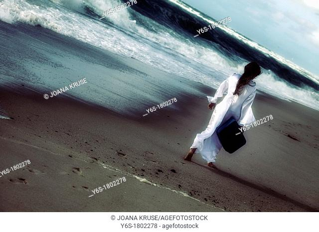 a girl in a white dress at the sea with a suitcase