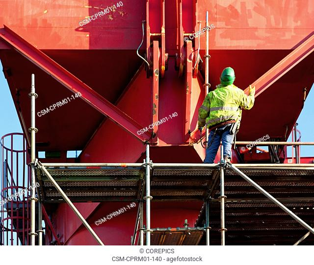 Industrial worker standing on scaffolding around a steel structure, looking up