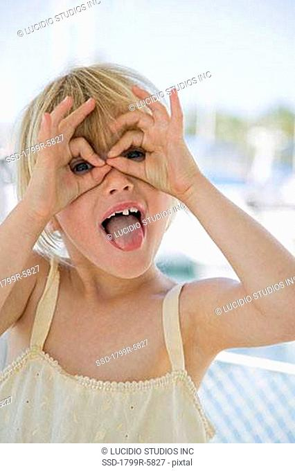 Close-up of a girl looking through the circle formed by her fingers