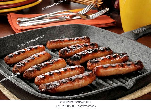 Grilled link sausage in a cast iron pan