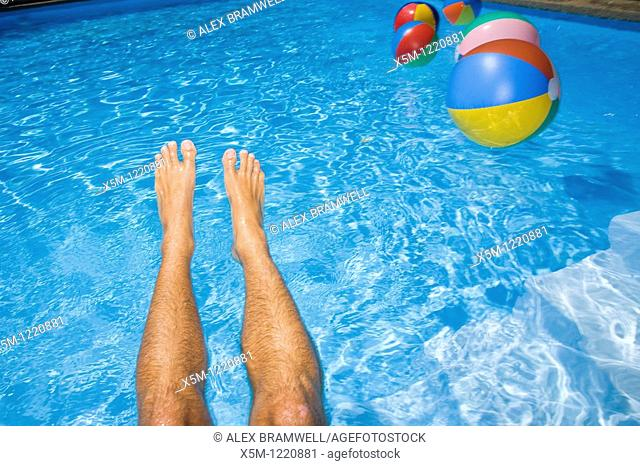 Blue pool with a pair of legs and some beach balls
