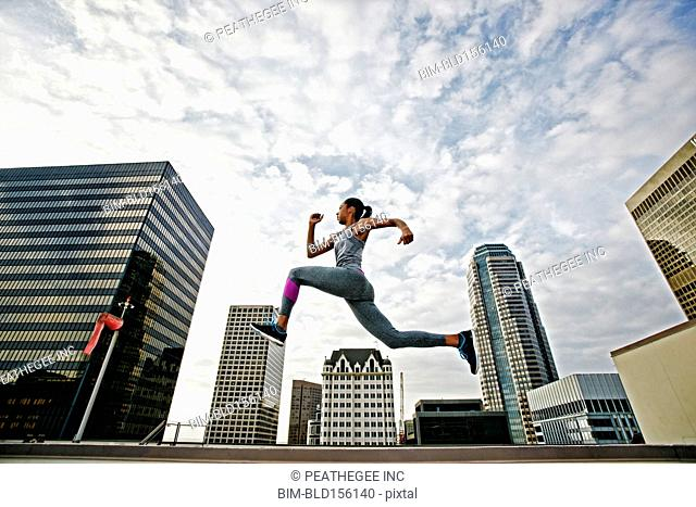 African American woman leaping on urban rooftop