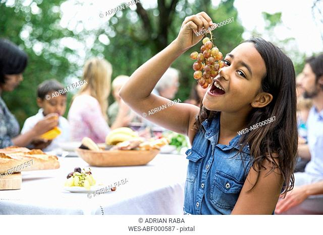 Girl eating grapes on a garden party