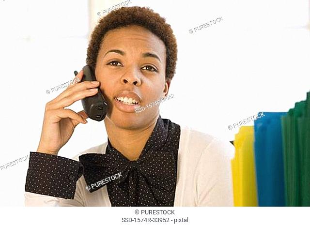 Close-up of a businesswoman talking on a cordless phone