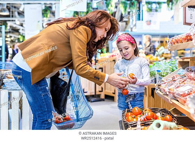 Mother and daughter buying tomatoes in supermarket