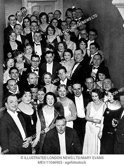 A large group of guests gathered on the stairs at the engagement party of comedienne, Nellie Wallace and Mr. J. Selwyn Smithurst at Warwick Square, London