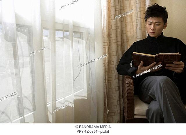 Young man reading at home
