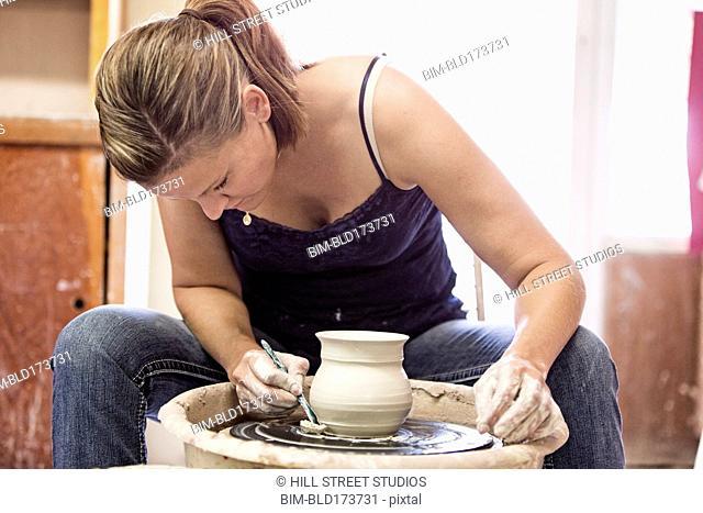 Caucasian student working on pottery wheel in studio