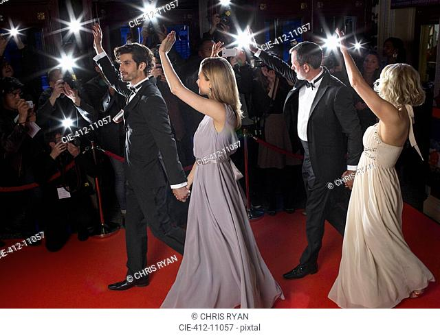 Well dressed celebrity couples waving to paparazzi on red carpet