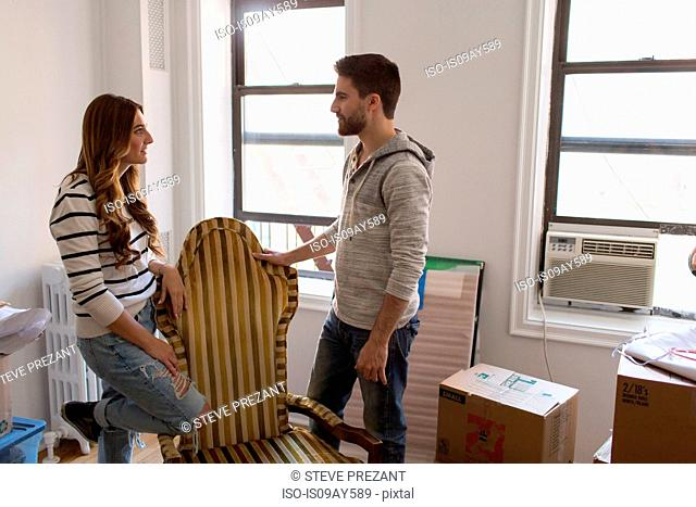 Moving house: Young couple leaning on chair having discussion