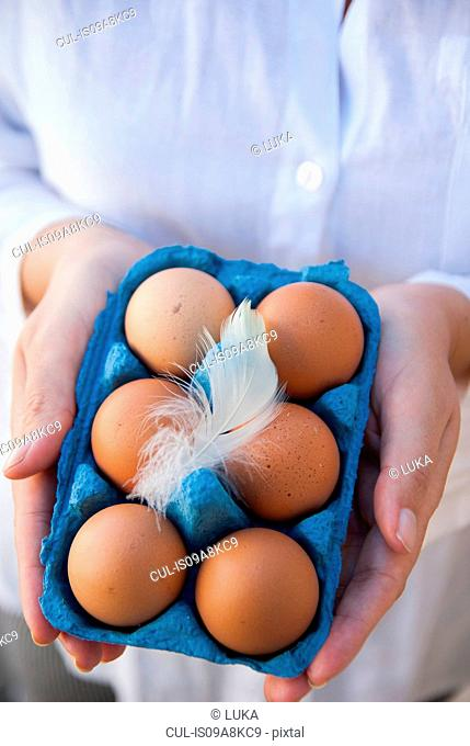 Woman holding six eggs in box with feather
