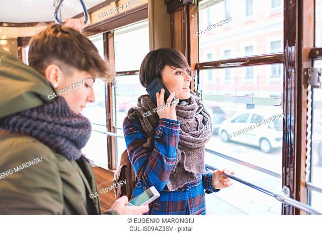 Two sisters riding cable car, using smartphones