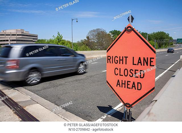 "Automobile passing a traffic sign on a highway reading """"Right Lane Closed Ahead"""""""""""