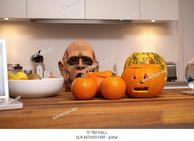 Jack-o-lanterns and mask in kitchen