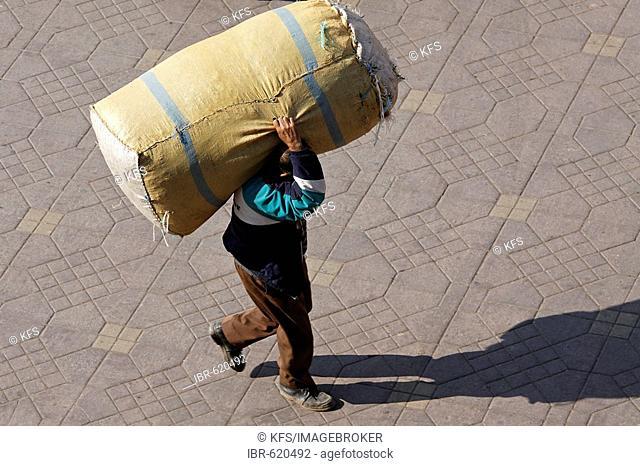 Man carrying a big parcel on his shoulders, Djemaa el Fna, Marrakech, Morocco, Africa
