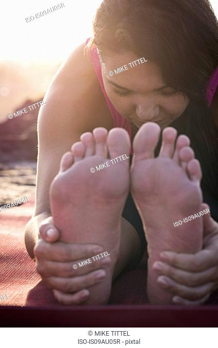 Close up of woman holding her feet practicing yoga at dawn