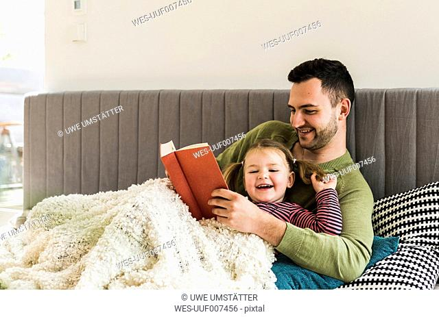 Happy father and daughter reading a book at home