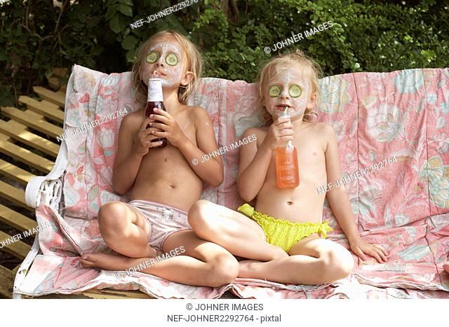 Girls drinking with beauty masks on faces