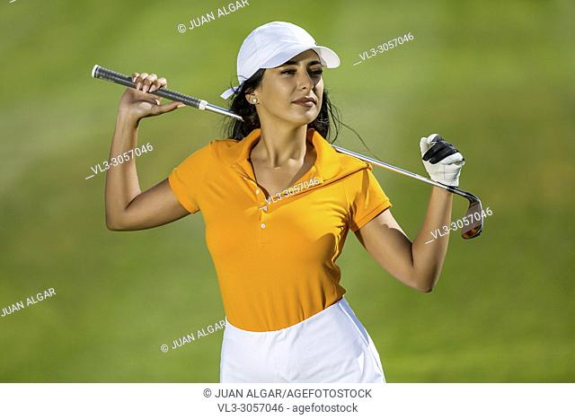 Stylish and sensual woman in colorful golf uniform holding driver and standing on green background in sunlight