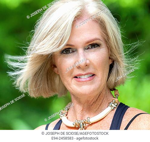 A portrait of a 56 year old blond woman smiling directly at the camera, outdoors.
