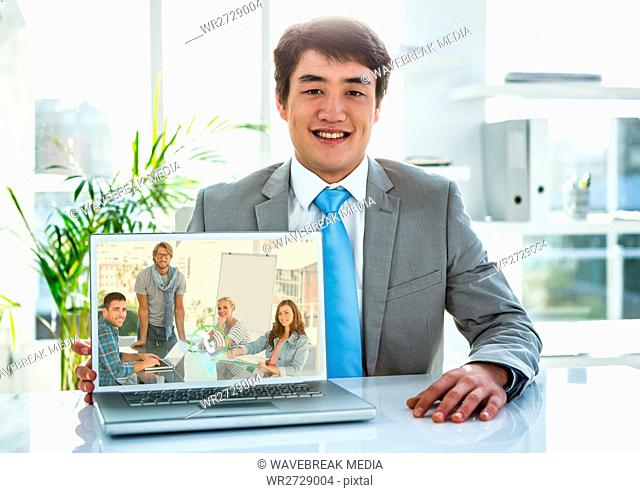 Portrait of businessman having video call on laptop in office